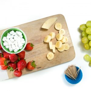 Cutting board with strawberries and cut bananas.