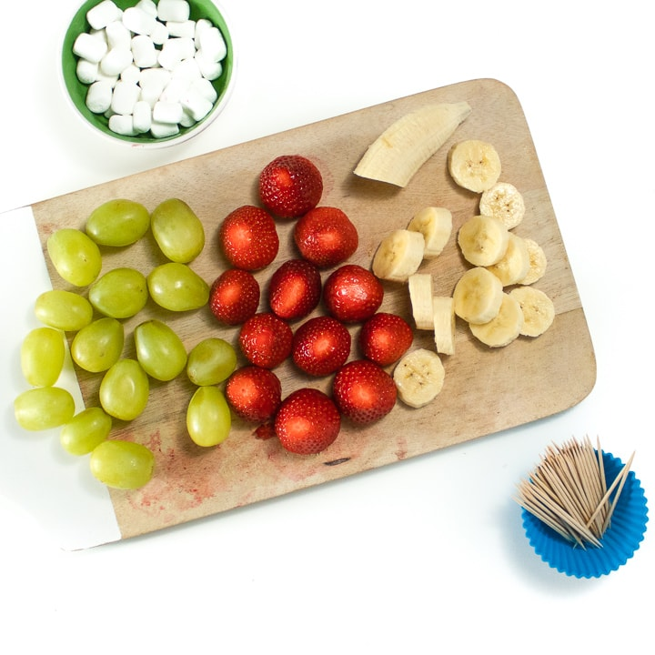 Cutting board with grapes, strawberries and sliced bananas for fruit kabobs.