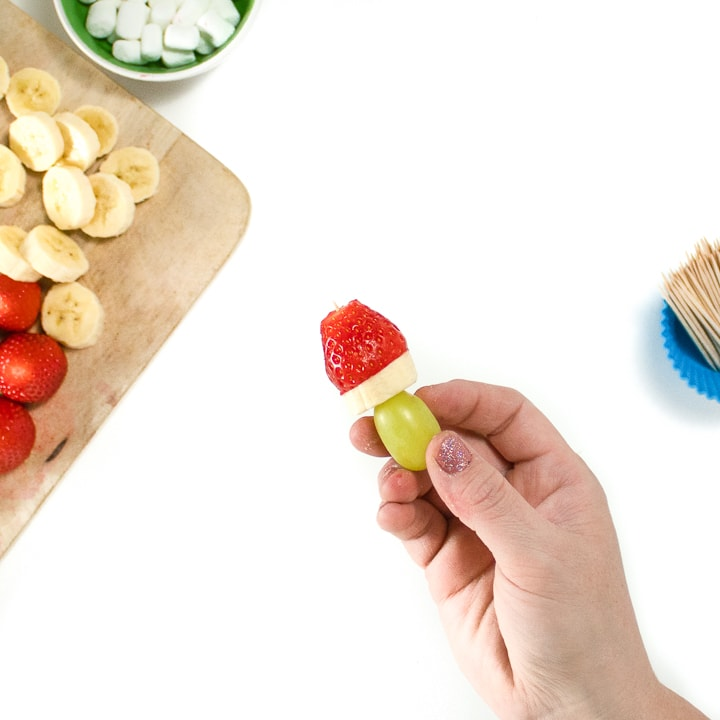 Hands holding a fruit pick grape, banana and strawberry on it.