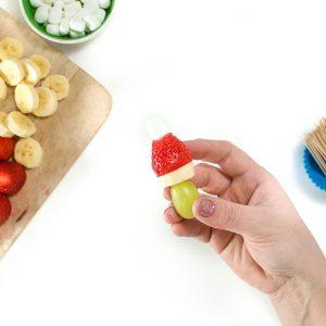 Hand holding a fruit kabob.