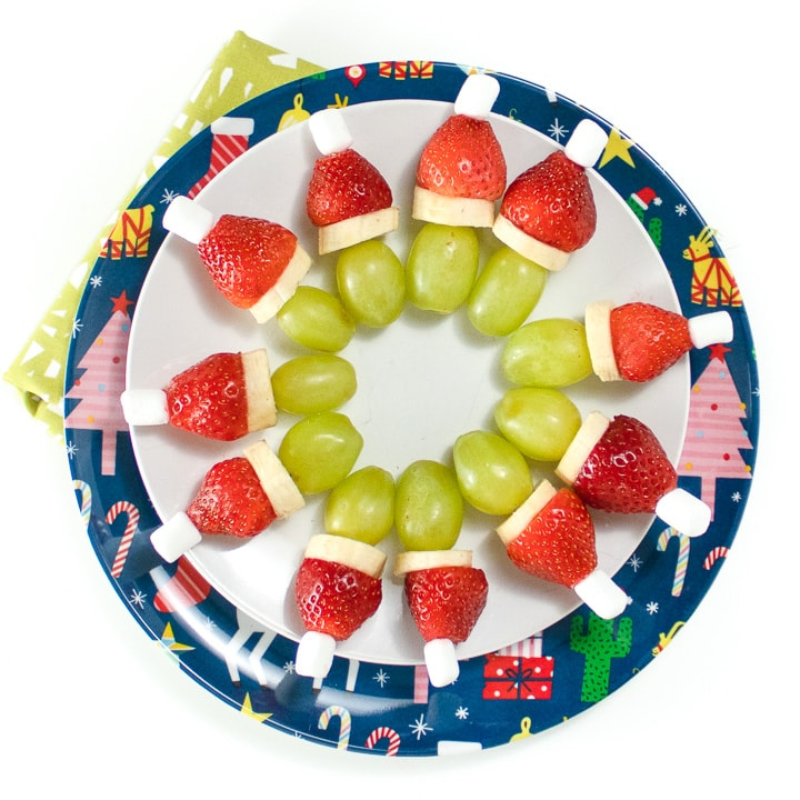 2 round plates with a circle of grinch kabobs on it.