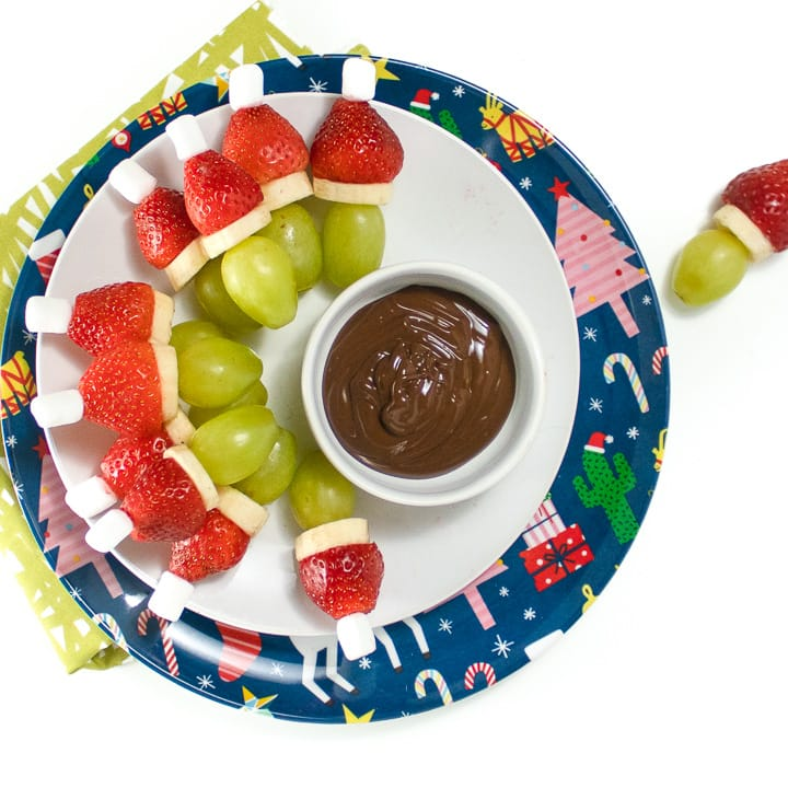 Round plate with grinch fruit kabobs on it.