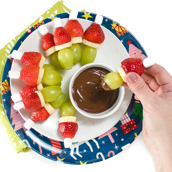 Round plate with grinch fruit kabobs in a circle with small bowl of chocolate dipping sauce.