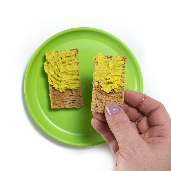 Hand holding a piece of toast with avocado and egg mashed together.