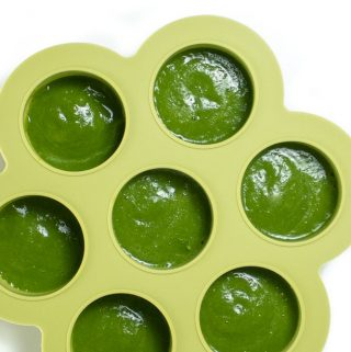 Green freezer tray with green bean puree inside.