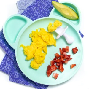 Teal plate on purple napkin with easy scrambled eggs, avocado and chopped strawberries.