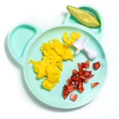Teal plate with breakfast for baby - scrambled eggs, avocado and chopped strawberries.