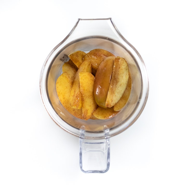 Small blender with chunks of apples in it.