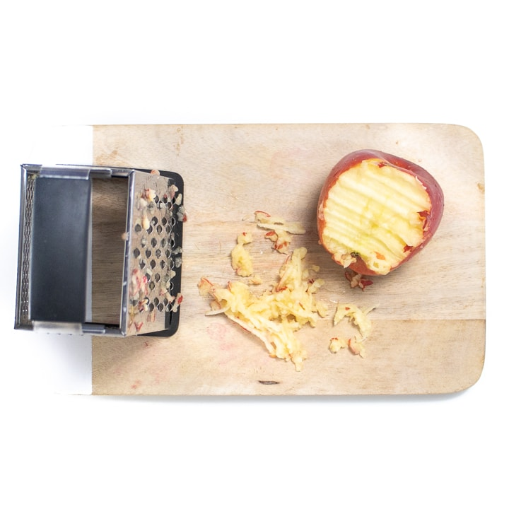 cutting board with an apple being grated.