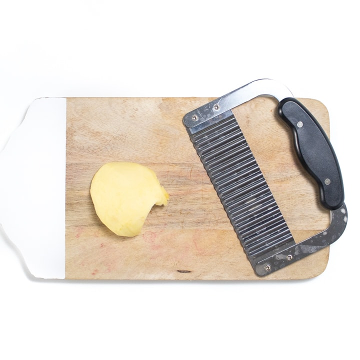 cutting board with an apple and a waffle knife.