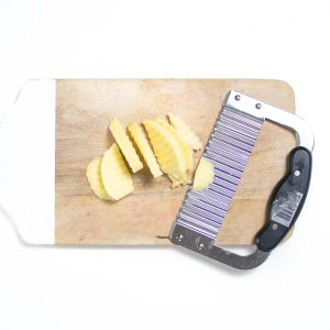 A Cutting board with a waffle knife with sliced apples for baby.