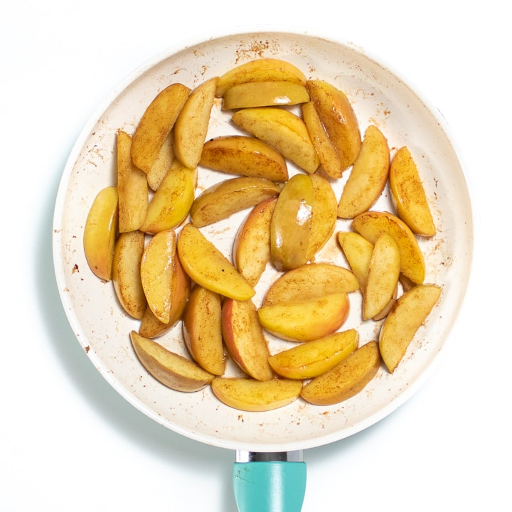 White skillet with apple slices for baby.