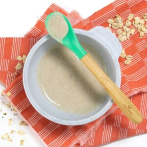 Gray baby bowl filled with oatmeal for babies with green spoon resting on top.