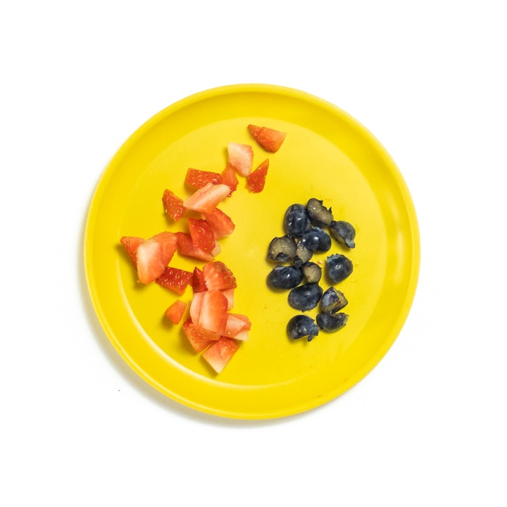 Yellow Plate with chopped fruit for baby.