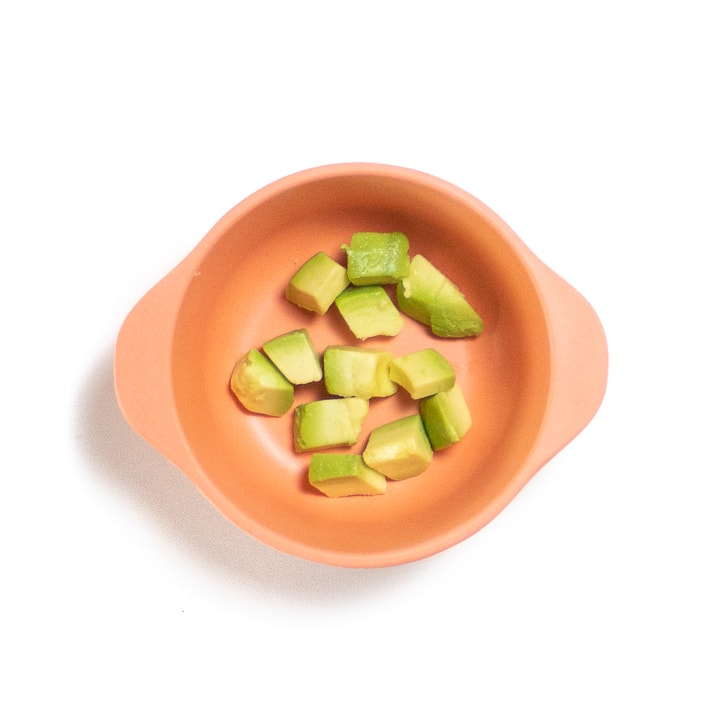 Small snack bowl full of chunks of avocado.