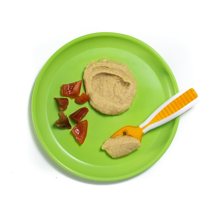 Plate with hummus and cut tomatoes for baby.