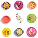 Grid of colorful kid plates with food for baby and toddler on it for snacks.
