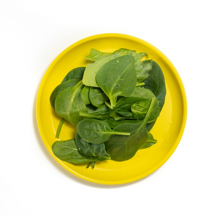 Yellow plate with spinach leaves on top.