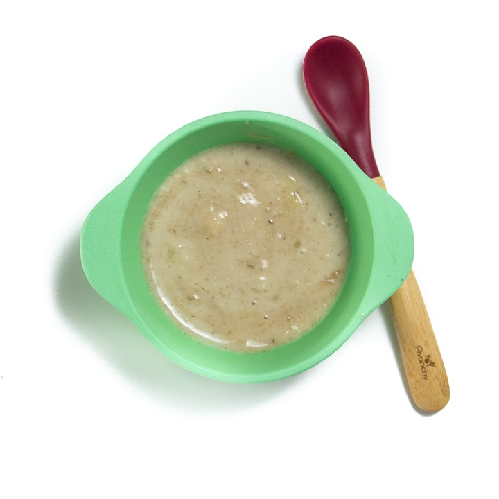 green baby bowl filled with oatmeal puree.
