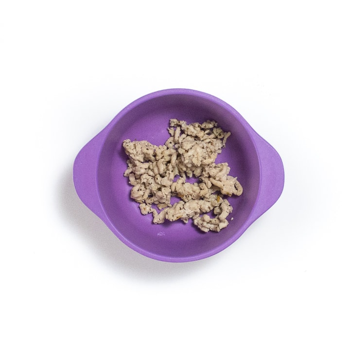 Hand holding a purple baby bowl filled with cooked ground chicken