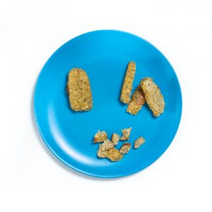 Blue baby plate filled with homemade meatballs whole and cut up for baby to feed themselves.
