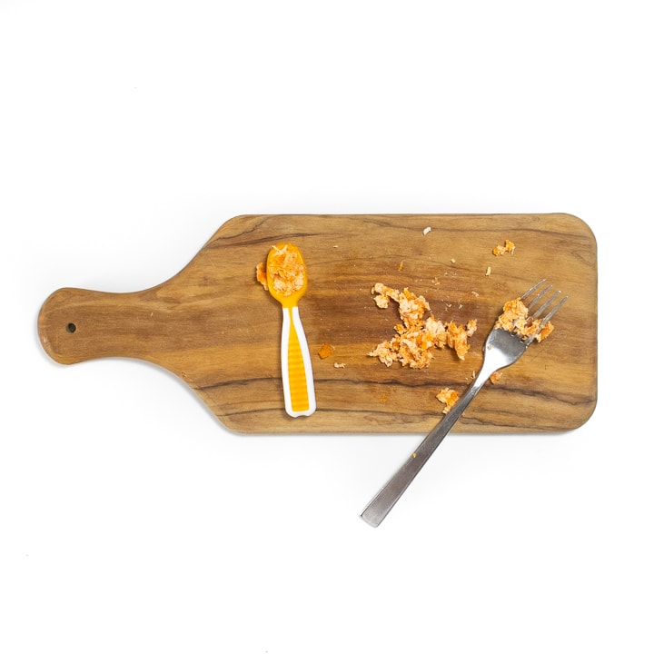 Cutting board with mashed cooked chicken and carrots.