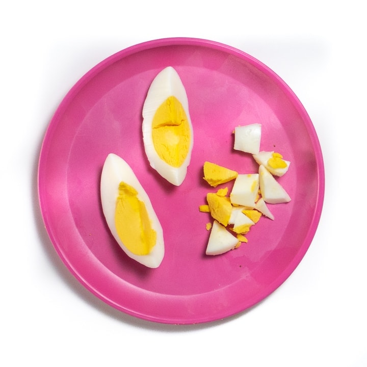 Pink baby plate filled with two way to serve hard boiled eggs.