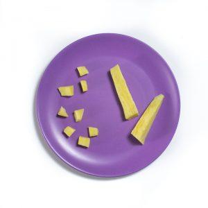 Steamed sweet potatoes on a purple plate.