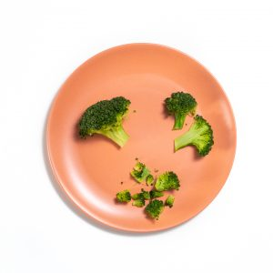 Orange baby plate with broccoli cut and chopped on it.