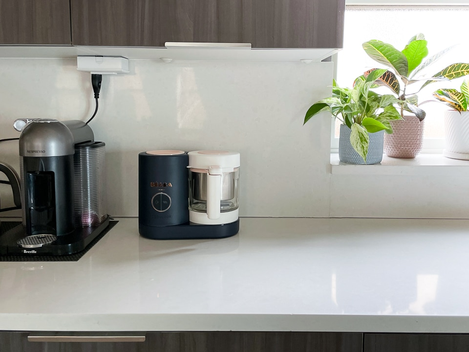 Black Beaba babycook on a white counter with a coffee machine and plant.