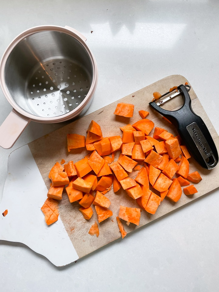 Wooden cutting board with chopped sweet potatoes a veggie peeler and the Beaba stainless steel basket sitting on a white counter.