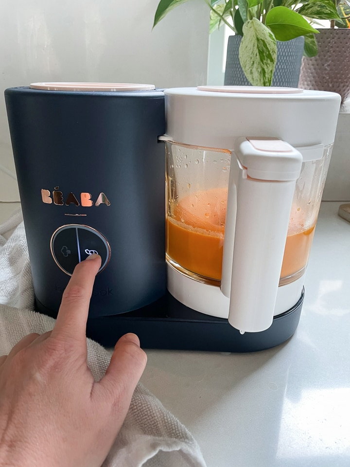 Hand hitting the blend button on a black Beaba babycook.