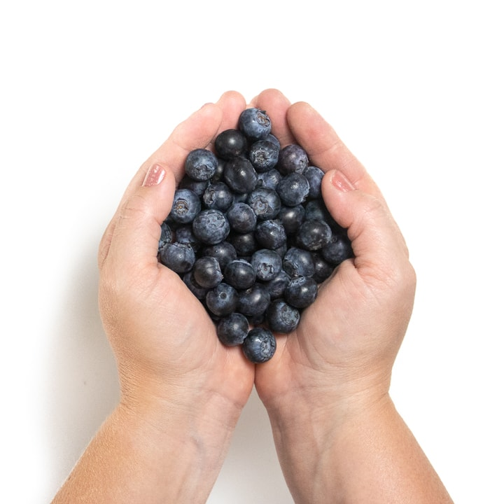 Hands holding blueberries.