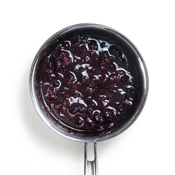 Saucepan full of simmered blueberries.