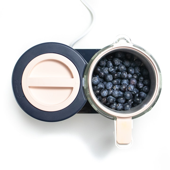 BEABA babycook with blueberries inside of the stainless steel container.