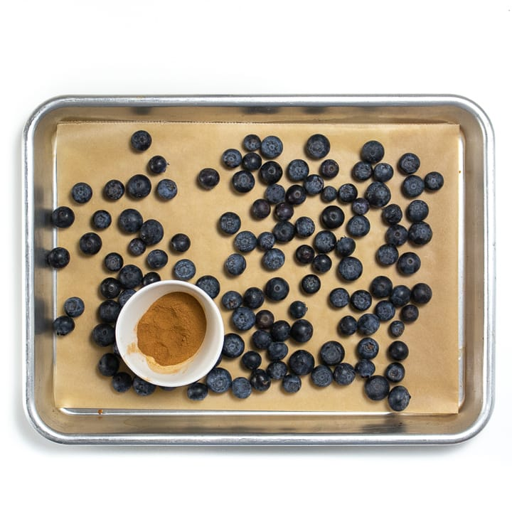 A baking sheet with blueberries and a small bowl of cinnamon.