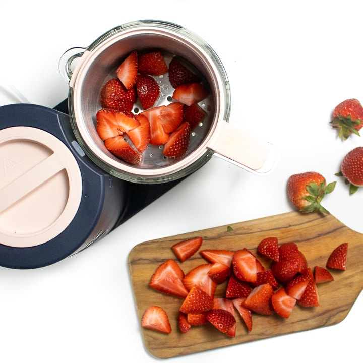 Beaba babycook with a cutting board with chopped strawberries.