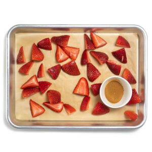 Baking sheet with fresh chopped strawberries and a small bowl of cinnamon.