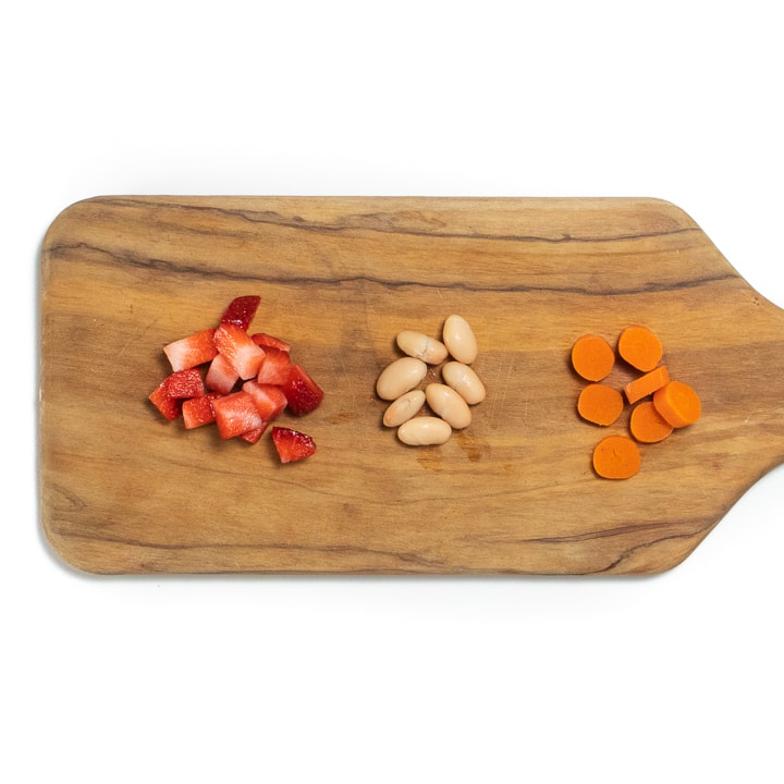 Cutting board with strawberries, beans and carrots.
