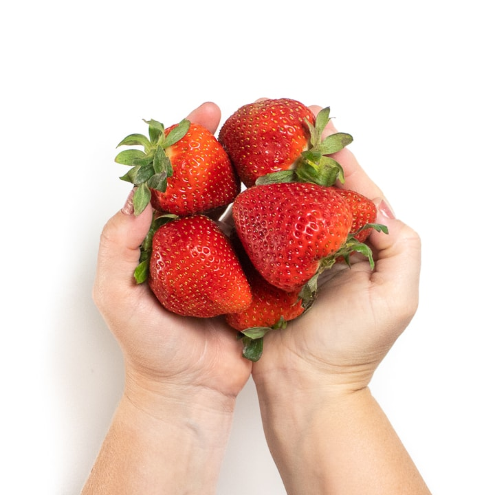 Hands holding fresh strawberries.