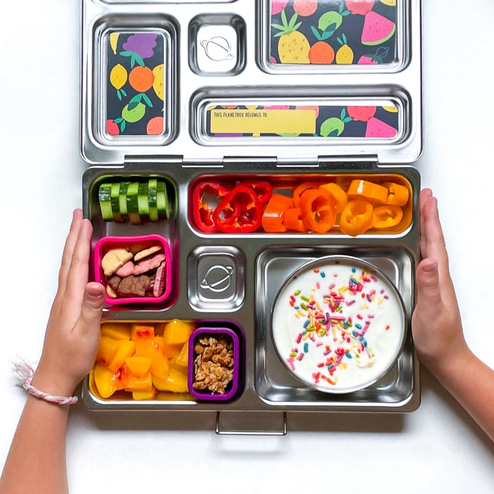 Small kids hands holding a metal lunch box filled with a healthy lunch.