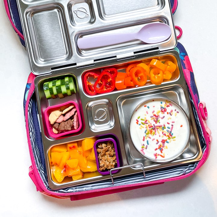 Planetbox lunch box filled with a colorful lunch is sitting inside a lunch box with a purple spoon resting on the lid.