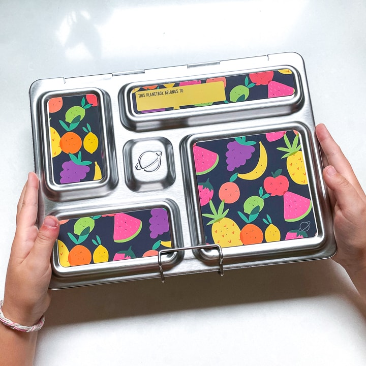 Small kids hands holding a closed planetbox lunch box with fruit magnets on the front.