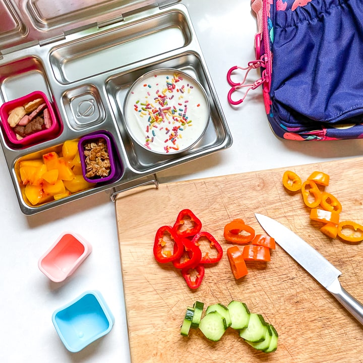 Cutting board with veggies and a planetbox lunch box sitting next to it halfway full with a kids lunch.