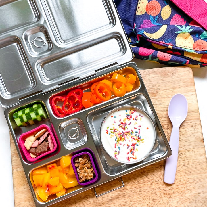 Planetbox on a cutting board filled with healthy and colorful food for a kids lunch with a purple spoon rising next to it.