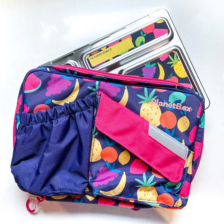 planetbox carrying case with fruit on a purple background with a silver lunch box sticking out of the top.
