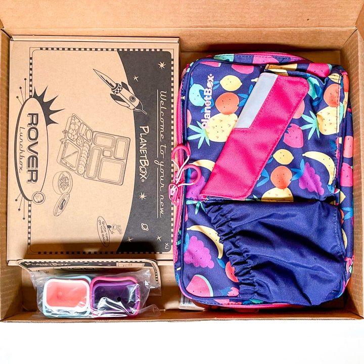 Cardboard box filled with a planetbox, accessories and a carrying case.