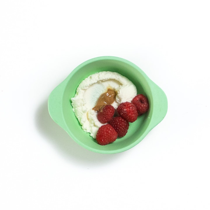 Green bowl full of a few raspberries, ricotta and nut butter.