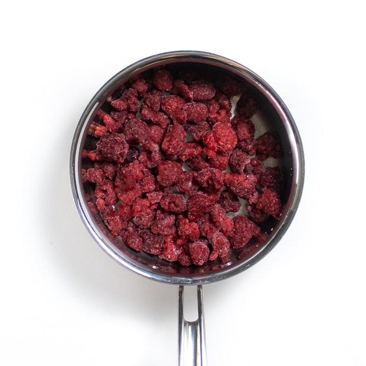 Sliver saucepan with frozen raspberries in it.